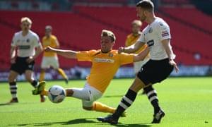 Liam Hughes of Cambridge United battles with Phil Turnbull of Gateshead.