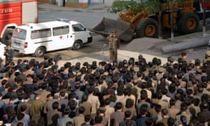 This picture released from North Korea's official KCNA news agency on 18 May, 2014, shows a construction officer (top) apologising to residents the collapse of a Pyongyang apartment building.