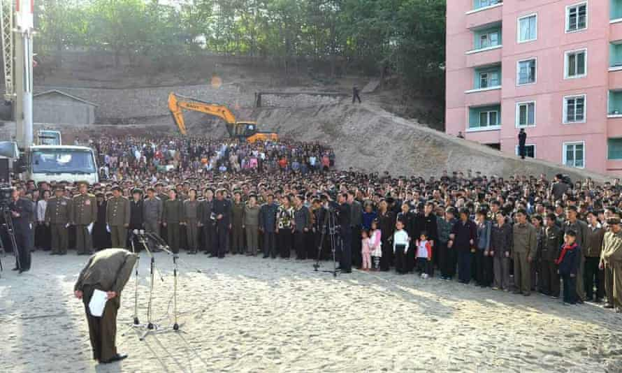 A handout photo by the North Korean state-run newspaper Rodong Sinmun shows a North Korean official (L) bowing in apology to citizens over an apartment building collapse at a construction site in Pyongyang.