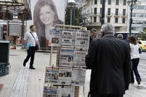 A man reads newspaper's headlines about the results of the first round of the local elections in central Athenson May 19, 2014.