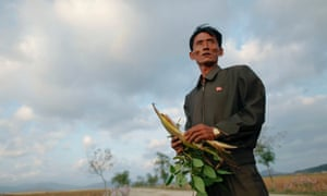 Pak Su-dong, manager of the Soksa-Ri cooperative farm in the area hit by floods and typhoons, shows damage to agricultural products in 2011.