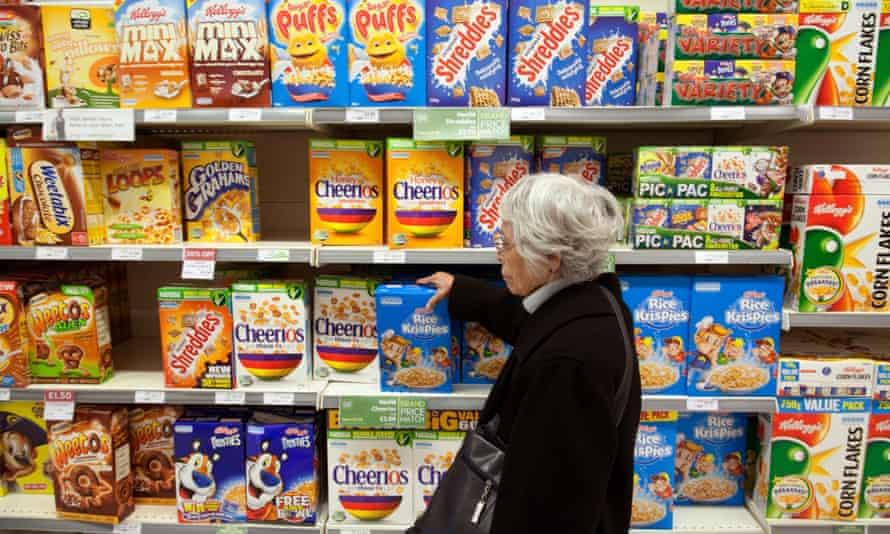 Elderly woman buying breakfast cereals from supermarket shelves,UK, on 27 November 2011.