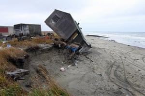 A home destroyed by beach erosion tips over 27 September 2006 in the the Alaskan village of Shishmaref