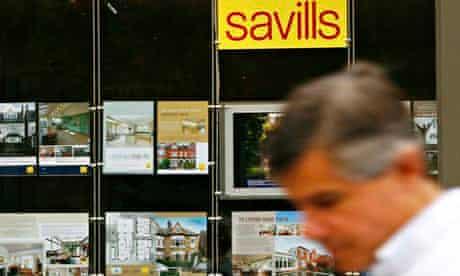 A pedestrian walks past a branch of Savills
