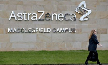 A woman walks by British pharmaceutical company AstraZeneca's Macclesfield campus