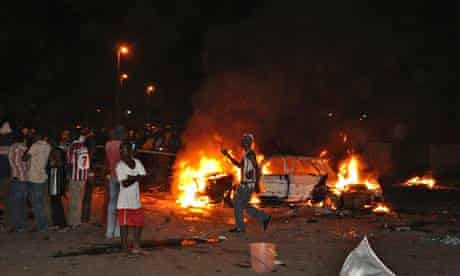People gather at the site of a car bomb explosion in Abuja, the capital of  Nigeria.