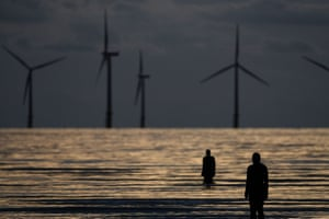 Figures from Antony Gormley's art installation Another Place in front of the turbines of the Burbo Bank offshore windfarm in the mouth of the river Mersey