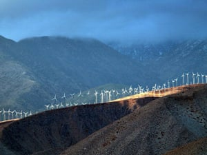 A band of sunlight shines through storm clouds to illuminate wind generators near Palm Springs, California