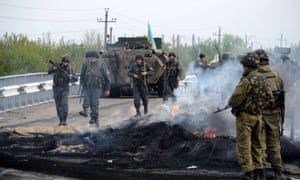 Ukrainian soldiers stand at a checkpoint, which they seized in the early morning in the village of Andreevka, 7 km from the centre of the southern Ukrainian city of Slavyansk, on May 2, 2014. Ukraine's military lost two helicopters and two servicemen on May 2 in a deadly offensive launched just before dawn against pro-Russian rebels holding the flashpoint town of Slavyansk, insurgents and authorities said.