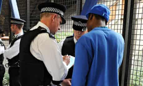 Metropolitan police officers question a man during a stop-and-search operation