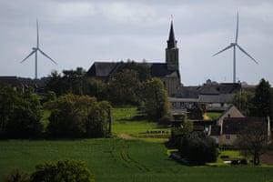 Wind turbines are seen in the Landes de Couesme wind farm near La Gacilly seen near the church in Saint-Nicolas-du-Tertre, western France, April 26, 2014.
