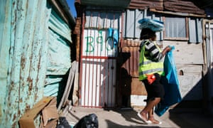 A South African municipal worker services shacks with bin bags in the informal settlement of Masiphumelele, Cape Town. Poor infrastructure and lack of services is a major issue facing the ruling party African National Congress (ANC)