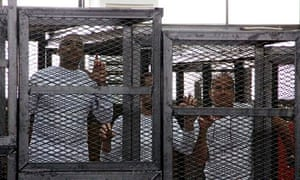 Jailed al-Jazeera journalists Mohamed Fahmy, Baher Mohamed and Peter Greste in a cage inside court