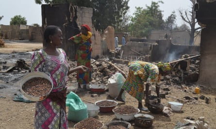 Women gather in front of a burnt-out house in Mainok, outside Maiduguri in Borno State. At least 74 people were killed in attacks on 1 March  2014 in villages near Maiduguri, blamed on Boko Haram militants.