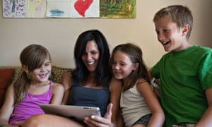 Mother and her three kids looking at an ipad together at home and smiling.