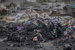 20 Photos: An Indian boy looks for metal scrap after a fire at a slum in Ghaziabad
