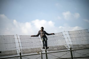 20 Photos: An African migrant on a border fence between Morocco and Spain