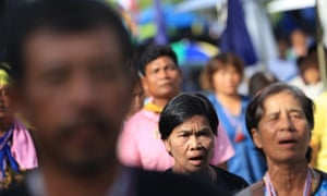 Anti-government protesters listen to their national anthem during a gathering Tuesday, May 20, 2014 in Bangkok, Thailand. Thailand's army declared martial law in a surprise announcement before dawn Tuesday that it said was aimed at keeping the country stable after six months of sometimes violent political unrest. The military, however, denied a coup d'etat was underway.