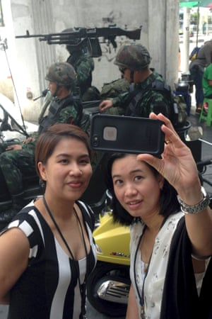 Residents stop to take a photograph of themselves at a military checkpoint in central Bangkok. Photograph: Kiko Rosario)/AP