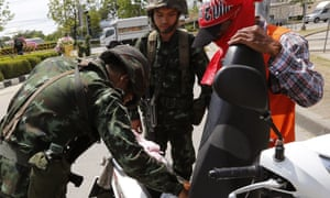 Thai armed soldiers check a motorbike of a Red Shirts pro-government supporter at a checkpoint near a rally site on the outskirts of Bangkok, Thailand, 20 May 2014.
