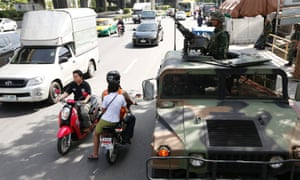 Thai soldiers take to the streets with a heavy machine gun on a Humvee military vehicle at a main road outside the Royal Thai Police Sports Club in Bangkok.
