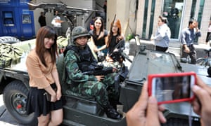 A woman poses for a photo with Thai army soldiers standing guard on a city centre street after martial law was declared