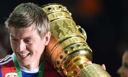 Bayern Munich midfielder Toni Kroos celebrates with the German Cup final trophy.