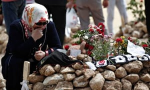 A woman mourns at the graves for miners who died in Tuesday's mine disaster, at a cemetery in Soma