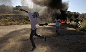 A Palestinian throws a stone during clashes with Israeli security forces outside Ofer prison