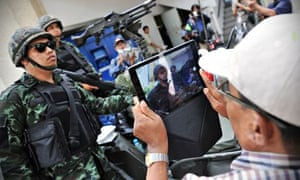 A tourist with soldiers driving through a Bangkok street after martial law was declared in Thailand