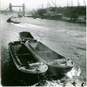 A view of the Pool of London from London Bridge with Tower Bridge in the background. The boats in the foreground would have transported cargo up and down the river to factories and warehouses c. 1935.
