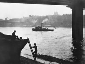 An early morning view of HIbernia Wharves, Southwark Cathedral and London Bridge, seen from underneath Southwark Bridge in the 1930s.