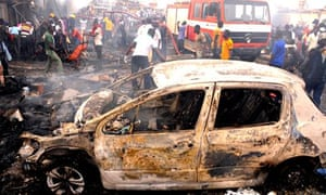 Firefighters and rescuers extinguish a fire following a bomb blast in central Jos, Nigeria.