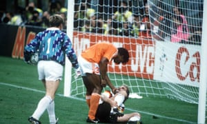 Frank Rijkaard encourages Rudi Voeller to get up after an angry confrontation in the box.