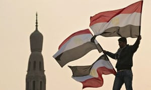 A youth waves Egyptian flags from a lamp post in Tahrir Square on February 1, 2011 in Cairo, Egypt