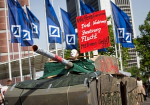 epa04218386 A demonstrator sits in a tank made ??of cardboard to protest against the bank's participation in the armaments industry  during the general meeting of Deutsche Bank at the Festhalle in Frankfurt am Main, Germany, 22 May 2014.