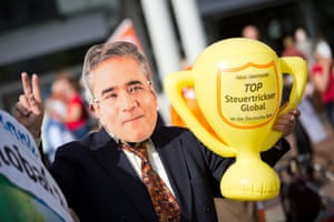 epa04218385 A demonstrator wears a mask of Deutsche Bank Co-CEO Anshu Jain and holds a cup reading 'Top global tax juggler' as he protests during the general meeting of Deutsche Bank at the Festhalle in Frankfurt am Main, Germany, 22 May 2014.