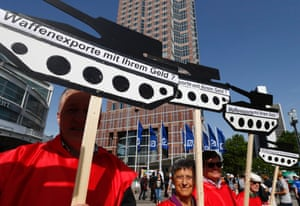 """Protesters hold placards reading: """"Arms exports financed with your money?"""" during a demonstration at the Deutsche Bank AG shareholders meeting in Frankfurt May 22, 2014."""