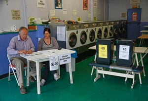 Poll clerks in a launderette being used as a polling station in Oxford.