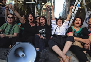 Fired cleaners of the Greek Finance ministry have occupied the ministry's entrance and shout slogans asking for the implementation of an Athens court ruling that ordered their re-hiring, in Athens, Greece, 22 May 2014.