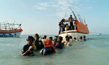 Somali migrants anxiously look back from the sea for relatives left behind on the beach as they wait