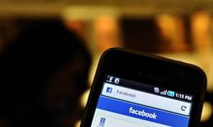 A man checks Facebook on his smartphone