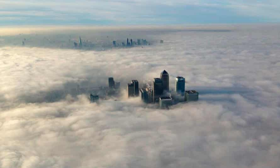 The Canary Wharf financial district (front) and the old City of London emerge from the fog.