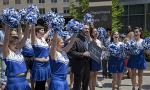 Greenpeace Climate and Policy Analyst Kyle Ash holds a photo album at the State Department in Washington with activists dressed as cheerleaders as they call on Secretary of State John Kerry to step up and protect the Arctic from oil drilling and the effects of climate change. Kerry will represent the United States at the Arctic Council meeting in May. The photo album is a collection of images from April 20 I Heart Arctic events across the United States on a global day of action.