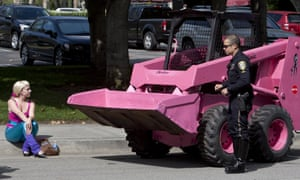 """A police officer questions a Greenpeace activist dressed as """"Barbie"""" outside Mattel headquarters where other activists dressed as 'Ken' dolls posted a giant banner with the message """"BARBIE: IT'S OVER. I DON'T DATE GIRLS THAT ARE INTO DEFORESTATION."""""""