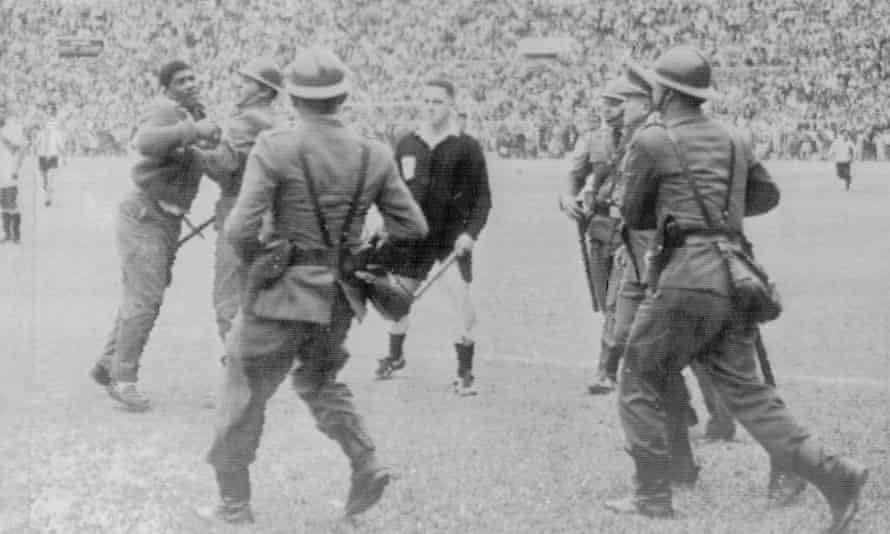 24 May 1964, Lima, Peru: Police restrain an angry football fan at the Estadio Nacional after a disallowed goal