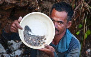 A man shows his yield of tin after a day's mining in a pit along a road near Airanyir, Merawang-Bangka, on the Indonesian island of Bangka.