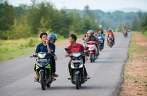 Youths drive their scooters along a road near Airanyir, Merawang-Bangka, on the Indonesian island of Bangka. Many citizens of Bangka start working in mining pits from a young age, by lack of alternatives to make a living.