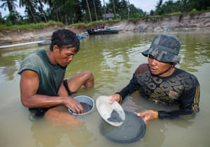 Two men check their yield of tin in a pit after a day's mining at a site near Samfur on the Indonesian island of Bangka.