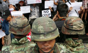 Thai soldiers in Bangkok are confronted by protesters opposing the military coup.